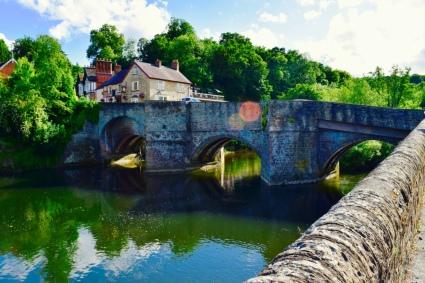 A pretty little lake an old style bridge.